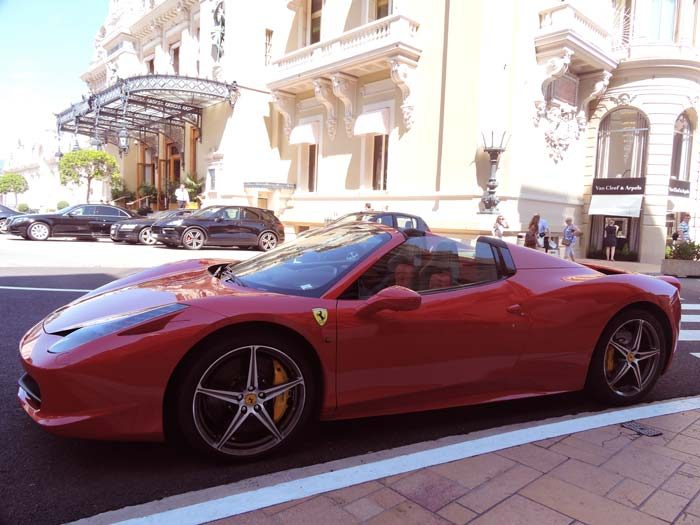 A red Ferrari sits in front of the Monte Carlo Casino