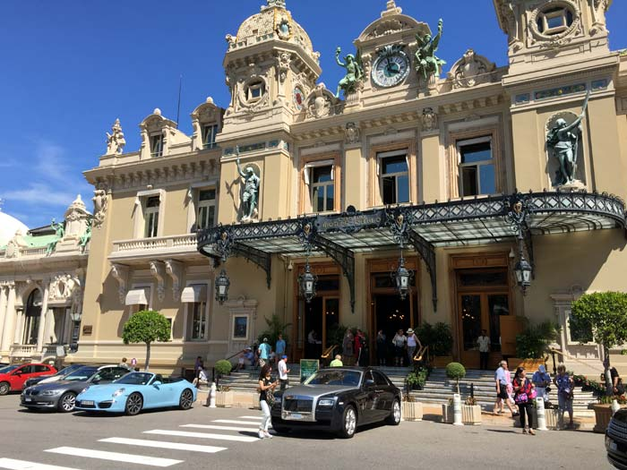 View of the front of the Monte Carlo Casino with beautiful cars lined up